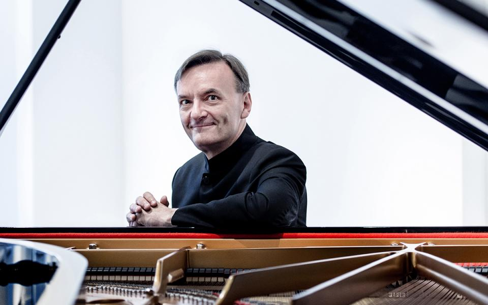 Pianist Stephen Hough, sitting at the piano, smiling at camera