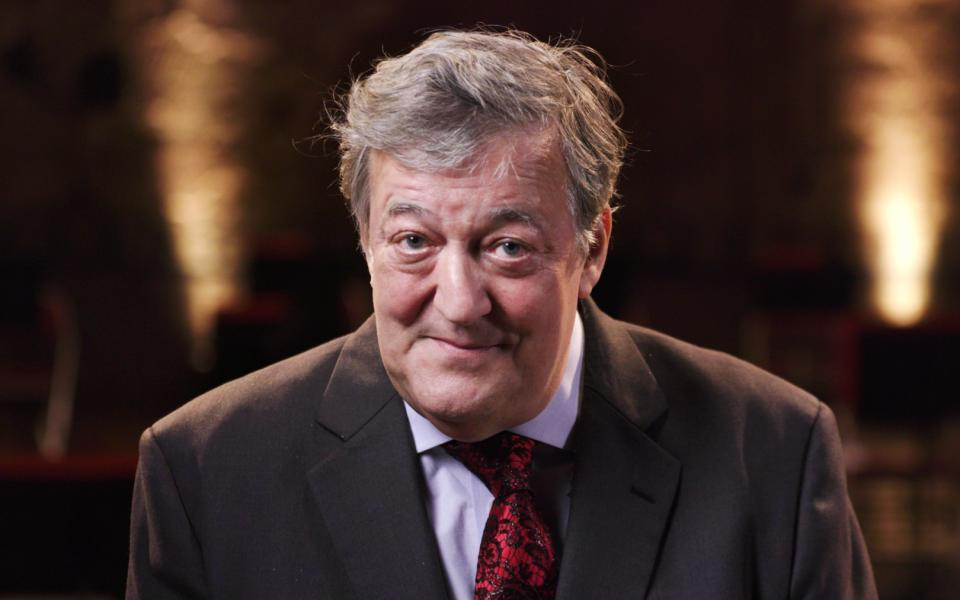 Stephen Fry looking at camera, wearing coat and red tie