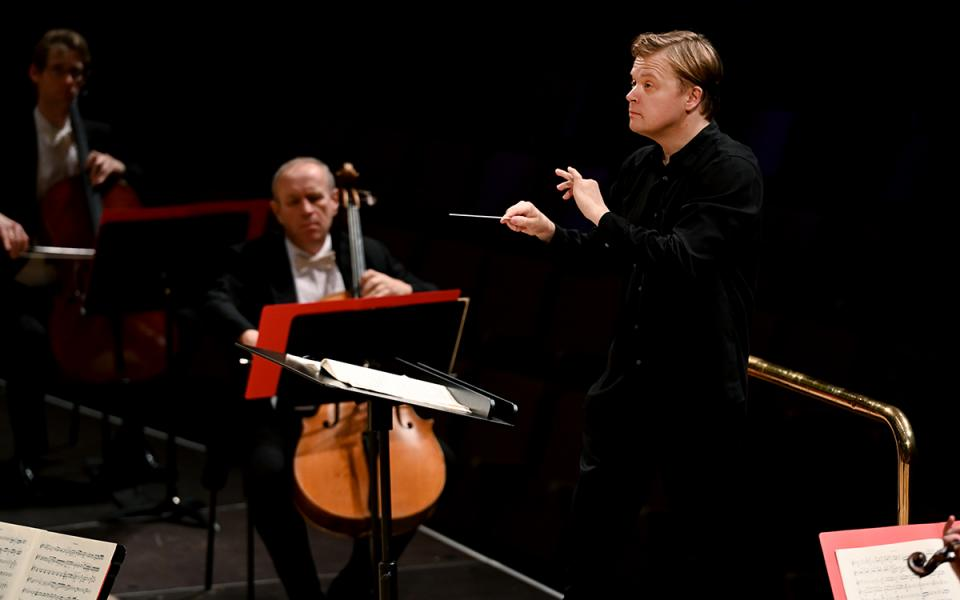 Pekka Kuusisto on stage conducting the Philharmonia, wearing black clothes, holding a baton