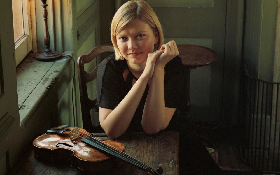 Violinist Aline Ibragimova, sitting at a table where rests a violin