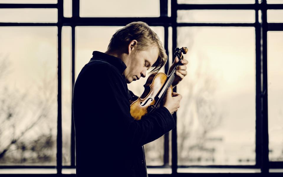 Pekka Kuusisto holding a violin