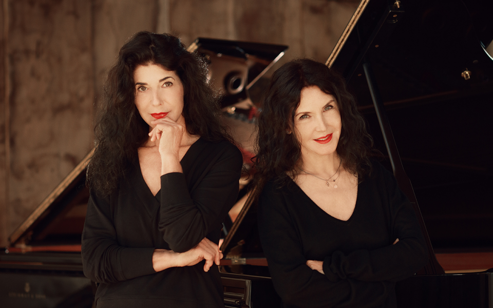 The pianists Katia and Marielle Labeque. The two women with long black hair and red lipstick look directly into the camera. In the background there are two Steinway Grand Pianos.