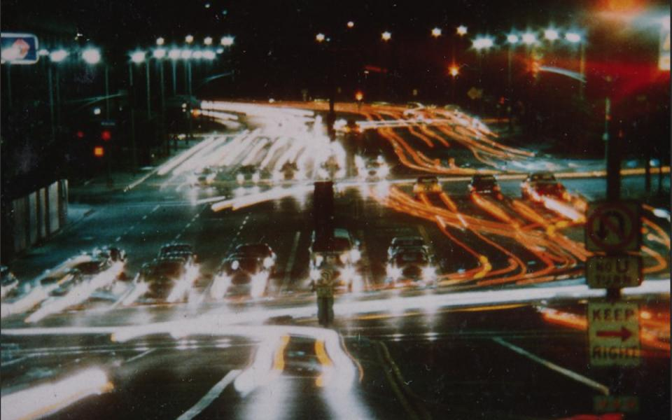Still from the film Koyaanisqatsi, showing cars in a highway at nighttime