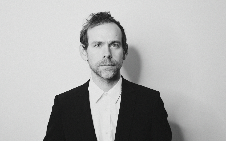 Photo of Bryce Dessner, credit Shervin Lainez. Image description: a black and whiteheadshot of the composer Bryce Dessner with a plain white background. A man with light skin wearing a shirt and suit jacket. He looks directly into the camera.